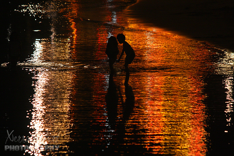 Children at Play on a Carnival Lit Beach