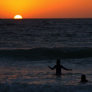 Sun down on Swimmers in Indian Ocean